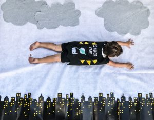Batman kids' birthday party decor; aerial shot of a toddler flying in a cape