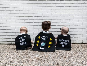 Batman kids' birthday party decor; toddler and babies in capes facing a brick wall