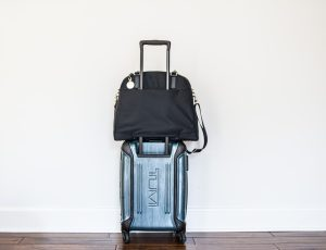 Black Lo and Sons Travel Bag on top of Tumi rolling carry on bag